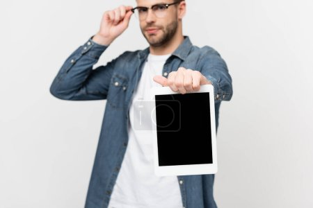 Photo for Digital tablet with blank screen in hand of man in eyeglasses on blurred background isolated on grey - Royalty Free Image