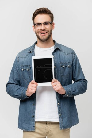 Smiling man in eyeglasses showing digital tablet isolated on grey