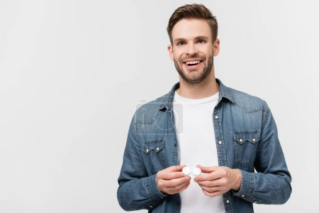 Smiling man holding case with contact lenses isolated on grey