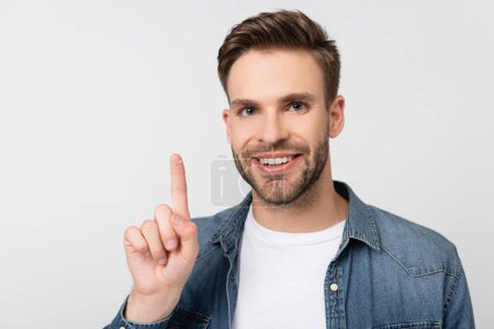 Smiling man looking at camera while holding contact lens isolated on grey