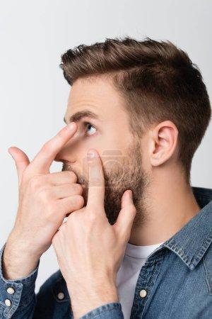 Photo pour Jeune homme détournant les yeux en portant une lentille de contact isolée sur gris - image libre de droit