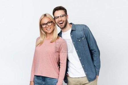 Photo pour Couple joyeux dans des lunettes regardant la caméra isolée sur gris - image libre de droit