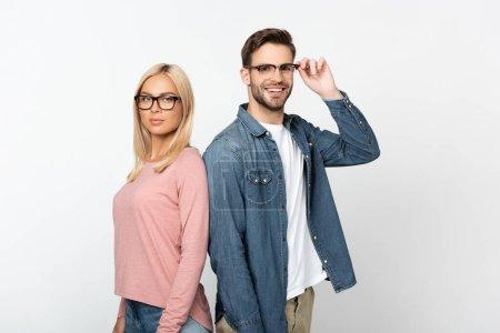 Smiling man touching optical eyeglasses near blonde girlfriend isolated on grey