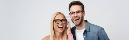 Photo for Cheerful couple in eyeglasses looking at camera isolated on grey, banner - Royalty Free Image