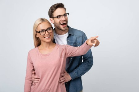 Photo for Cheerful man in eyeglasses embracing girlfriend pointing with finger isolated on grey - Royalty Free Image