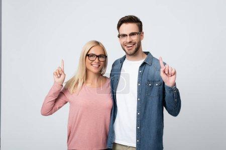Photo pour Couple souriant à lunettes pointant les doigts isolés sur le gris - image libre de droit