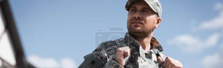 Photo pour Militaire sérieux avec sac à dos regardant loin avec ciel brouillé sur fond, bannière - image libre de droit
