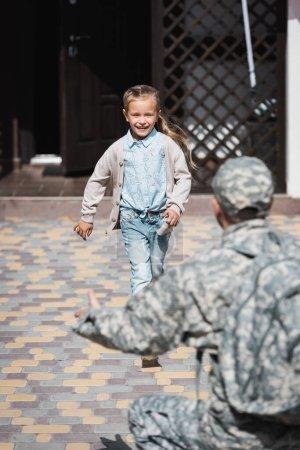 Photo pour Happy girl courir, avec un père flou en uniforme militaire au premier plan - image libre de droit