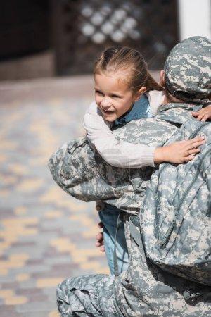 Photo pour Vue arrière de militaire homme étreignant fille souriante sur fond flou - image libre de droit