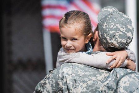 Photo pour Vue arrière de l'homme militaire embrassant sa fille souriante avec un drapeau américain flou sur fond - image libre de droit