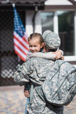 Photo pour Vue arrière de l'homme militaire avec sac à dos embrassant fille avec drapeau américain flou et maison sur fond - image libre de droit