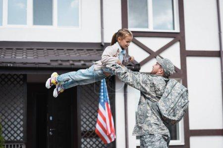 Photo pour Militaire levant fille souriante dans l'air près de la maison avec drapeau américain - image libre de droit