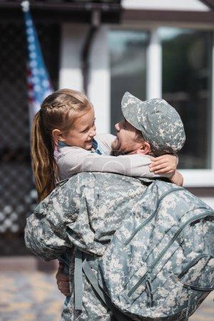Photo pour Père heureux en uniforme militaire embrassant fille sur fond flou - image libre de droit