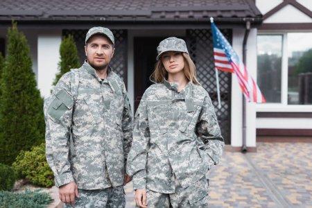 Photo pour Couple militaire en uniforme debout ensemble et regardant la caméra près de la maison - image libre de droit