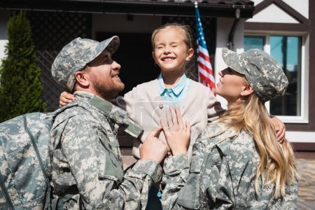 Photo for Happy daughter embracing father and mother in military uniforms near house with usa flag - Royalty Free Image