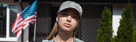 Ernste Militärfrau blickt in die Kamera in der Nähe von Haus mit amerikanischer Flagge, Banner