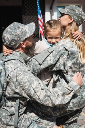 Photo for Upset daughter hugging mother and father in military uniforms near house with american flag - Royalty Free Image