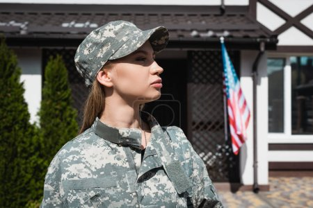Profile of confident military woman in uniform looking away with blurred american flag and house on background