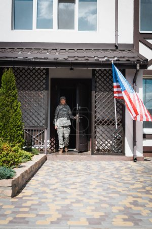 Photo for Military servicewoman standing in doorway near american flag and bushes - Royalty Free Image