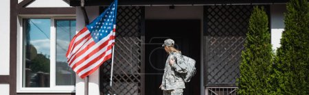 Military servicewoman with backpack leaving house, standing on threshold, banner