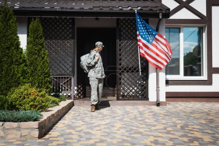 Photo for Military servicewoman with backpack leaving house, standing on threshold - Royalty Free Image