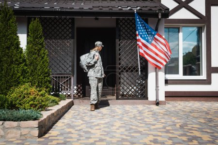 Military servicewoman with backpack leaving house, standing on threshold