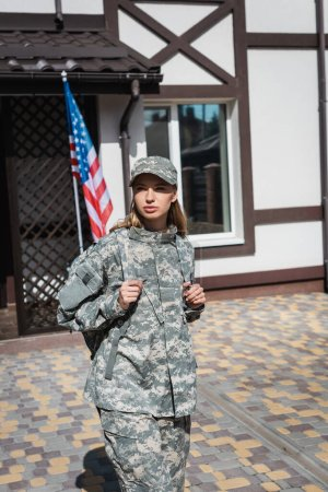Serious military servicewoman leaving house and looking away with usa flag and house on background
