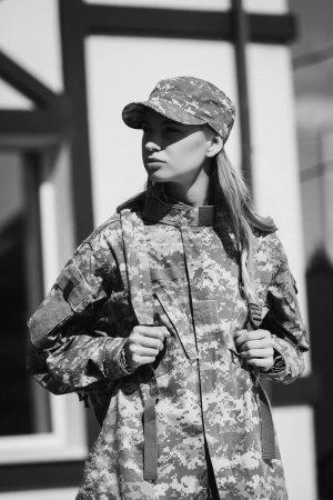 Photo pour Femme de service militaire confiante regardant ailleurs et tenant les bretelles du sac à dos sur fond flou, monochrome - image libre de droit