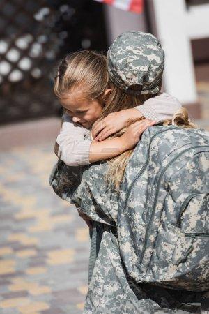 Photo pour Fille souriante étreignant la mère en uniforme militaire sur fond flou - image libre de droit