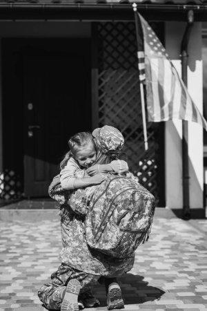Photo pour Femme militaire embrassant sa fille, assise à genoux près de la maison et drapeau américain, monochrome - image libre de droit