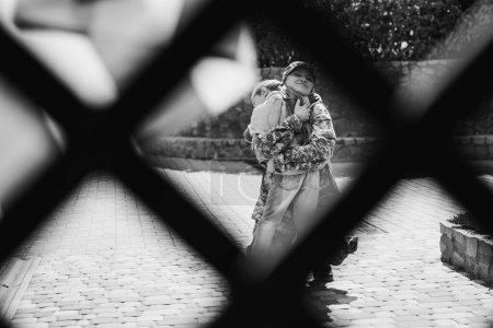 Photo pour Mère en uniforme militaire embrassant fille avec filet flou au premier plan, monochrome - image libre de droit