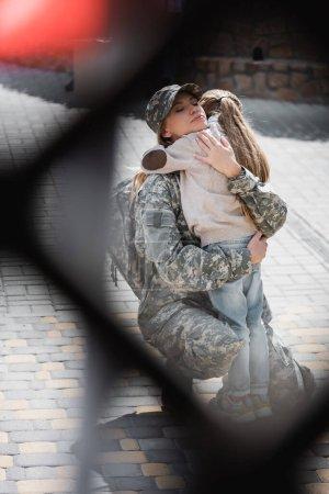 Photo pour Fille embrassant mère en uniforme militaire avec filet flou au premier plan, monochrome - image libre de droit
