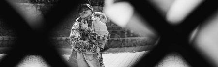 Photo pour Mère heureuse en uniforme militaire embrassant fille avec filet flou au premier plan, bannière, monochrome - image libre de droit