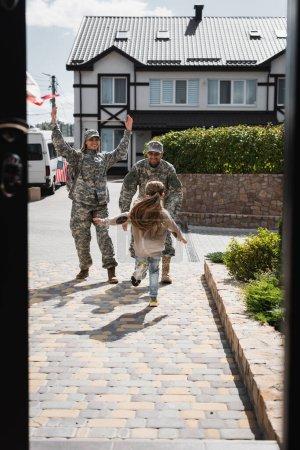 Photo pour Fille courant vers père et mère heureux en uniformes militaires dans la rue près de la maison au premier plan flou - image libre de droit