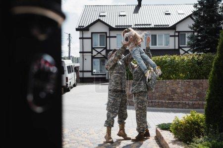 Photo pour Père et mère en uniforme militaire soulevant leur fille dans les airs, debout dans la rue au premier plan flou - image libre de droit