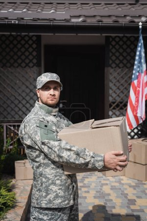 Photo for Military man holding cardboard box, while looking at camera near house and american flag - Royalty Free Image