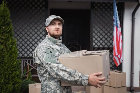 Military serviceman holding cardboard box, while looking away near house and american flag