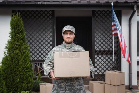 Photo for Front view of military serviceman with cardboard box standing near house with american flag - Royalty Free Image