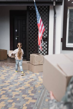 Little girl carrying cardboard box to house on blurred foreground