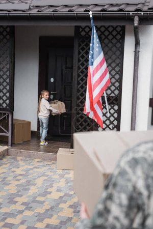 Smiling girl with cardboard box standing near house door with blurred father on foreground