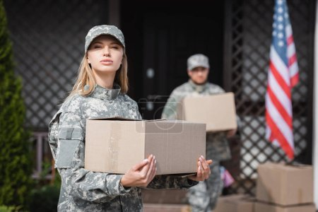 Confident woman in camouflage holding cardboard box and looking at camera with blurred military man on background