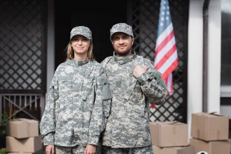 Smiling military couple looking at camera near cardboard boxes, with blurred house on background