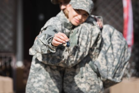 Keys with blurred military wife and husband hugging on background