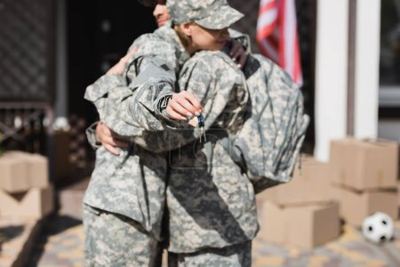 Military couple embracing and holding keys with blurred house and cardboard boxes on background