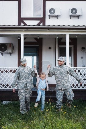 Photo for Smiling military father and mother lifting daughter over grass on backyard near house - Royalty Free Image
