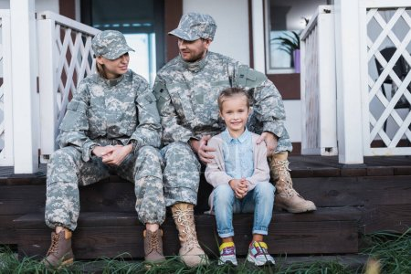 Photo for Smiling military father and mother with daughter sitting on house threshold - Royalty Free Image