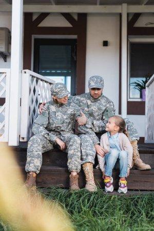 Photo pour Niveau de surface du père et de la mère militaires avec leur fille, assis sur le seuil de la maison au premier plan flou - image libre de droit