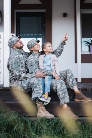Photo for Happy military mother and father pointing with finger, looking away, sitting with daughter on house threshold on blurred foreground - Royalty Free Image