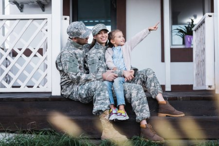 Photo for Smiling military mother and father hugging, sitting with daughter pointing with finger, on house threshold on blurred foreground - Royalty Free Image