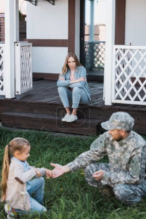 Woman with crossed arms sitting on house threshold on backyard with blurred military man and girl on foreground